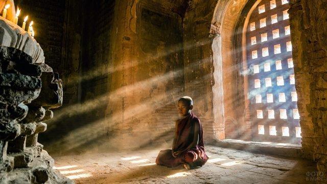 Юный буддистский монах в лучах вечернего солнца на полу Тибетского монастыря