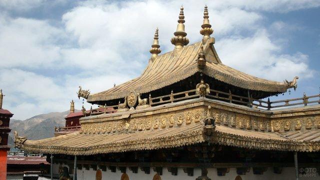 Крыша монастыря Джокханг в Лхасе на фоне Тибетских гор