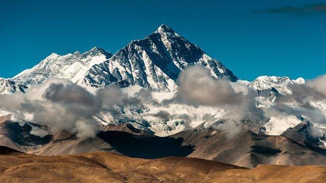 Облака на фоне заснеженных вершин Тибетских гор