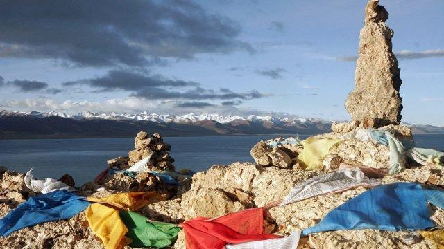 Ритуальный курган с флажками на фоне панорамы Тибетских вершин
