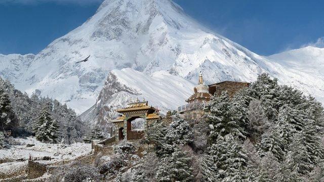 Тибетский монастырь среди заснеженного леса в горах