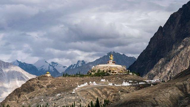 Тибетский монастырь в горах с большой статуей на возвышенности