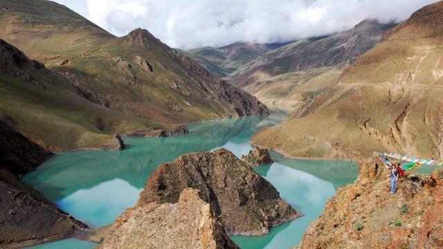 Туристка на обрыве над рекой в Тибете