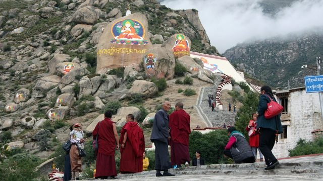 Туристы и тибетские монахи у подножья горного монастыря в Лхасе
