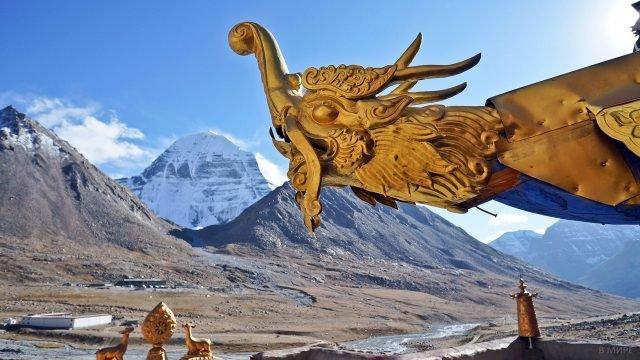 Украшение крыши монастыря Джокханг в Лхасе на фоне Тибетских гор