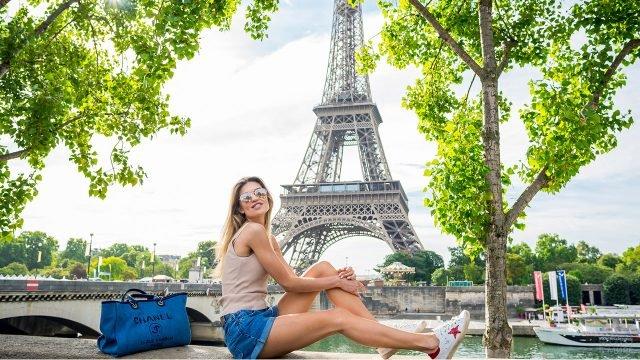 Блондинка на летней набережной Сены на фоне Эйфелевой башни