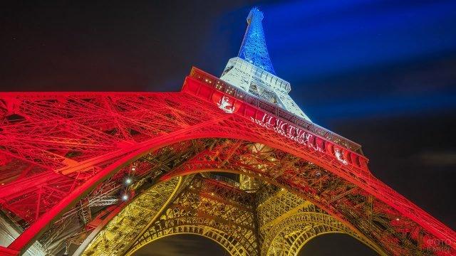 Эйфелева башня в цветах французского флага на фоне ночного неба