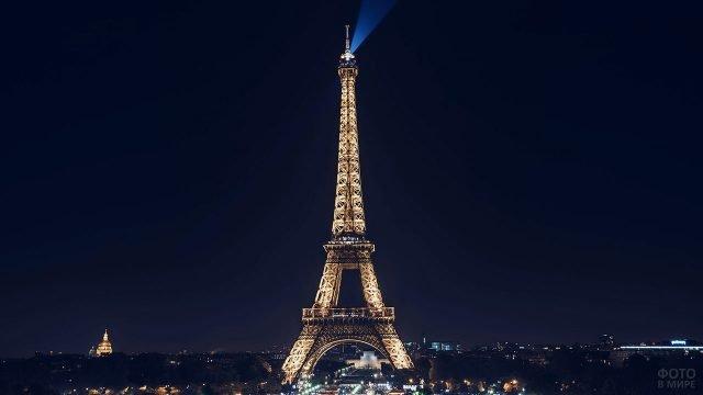Луч прожектора на верхушке освещённой в ночи Эйфелевой башни