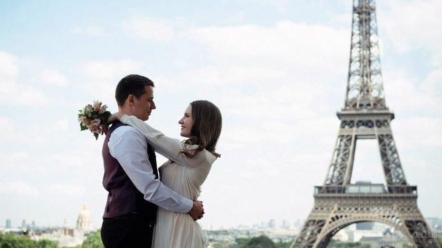 Обнимающиеся молодожёны на фоне Эйфелевой башни