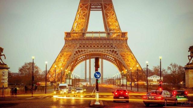 Огни вечерних авто под сводами опор Эйфелевой башни