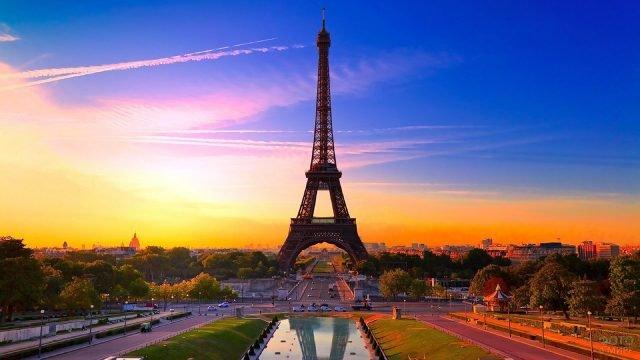 Силуэт Эйфелевой башни на фоне живописного заката над Елисейскими полями