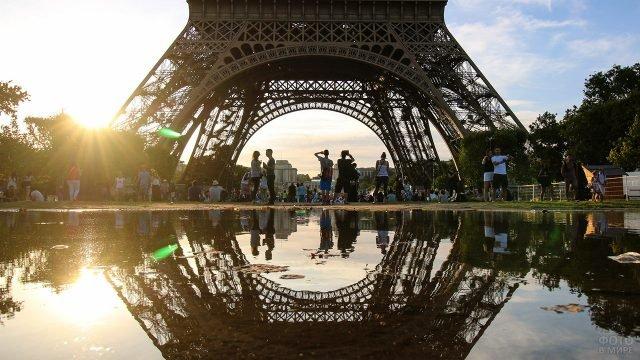 Силуэты туристов и отражение в воде у подножья Эйфелевой башни