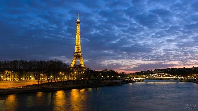 Светящаяся Эйфелева башня на вечерней набережной Сены