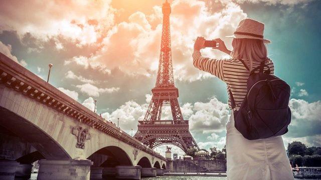 Туристка делает фото Эйфелевой башни с набережной Сены