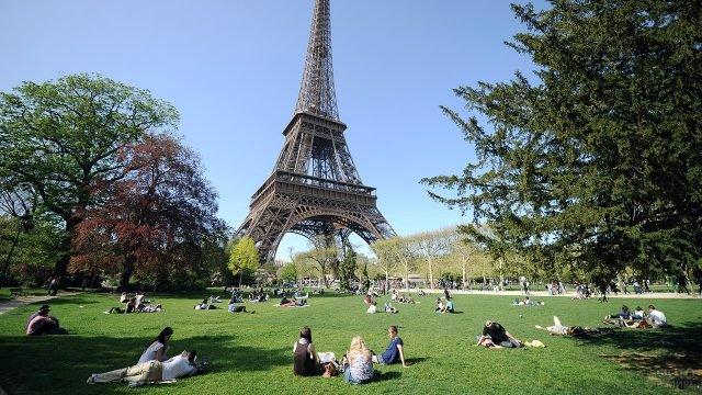 Туристы и парижане отдыхают на газоне у подножья Эйфелевой башни