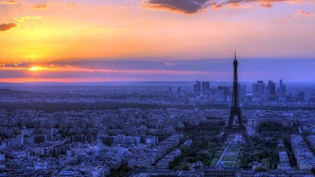 Закат над Парижем с силуэтом Эйфелевой башни среди зелени Елисейских полей