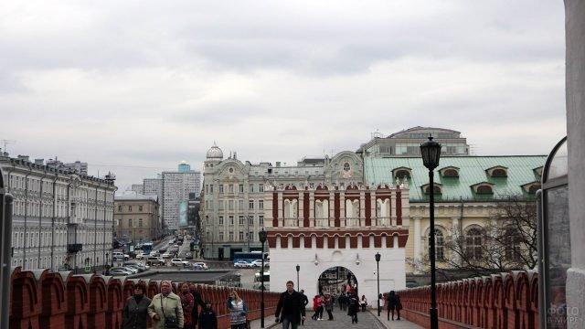 Туристы идут по мосту между Кутафьей и Троицкой башнями Кремля