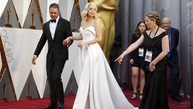 Леди Гага в сопровождении сотрудников церемонии Оскар выходит на красную дорожку в Голливуде