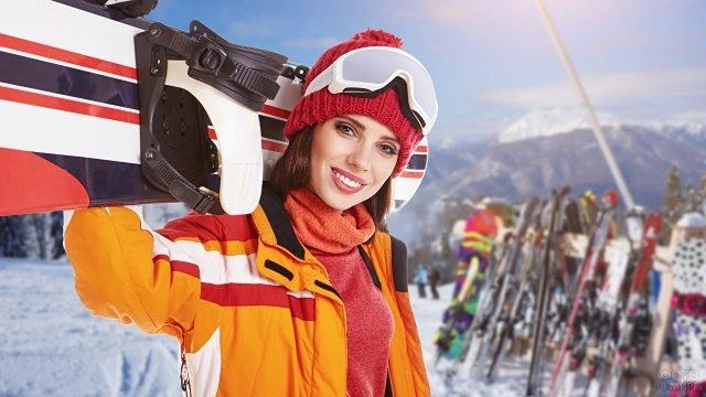 Девушка держит сноуборд на плечах