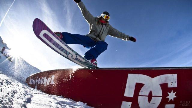 Девушка выполняет трюк на стойке со сноубордом