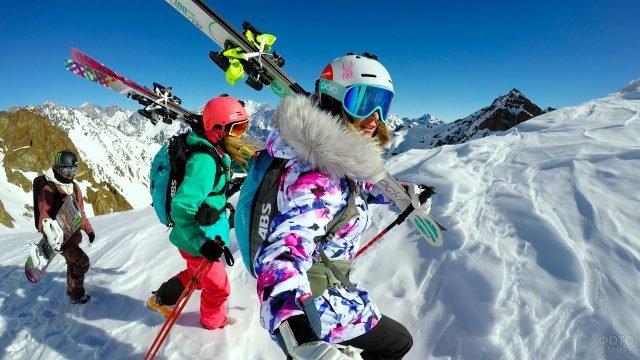 Девушки с лыжами и парень со сноубордом