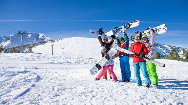 Компания сноубордистов делает групповое фото на память