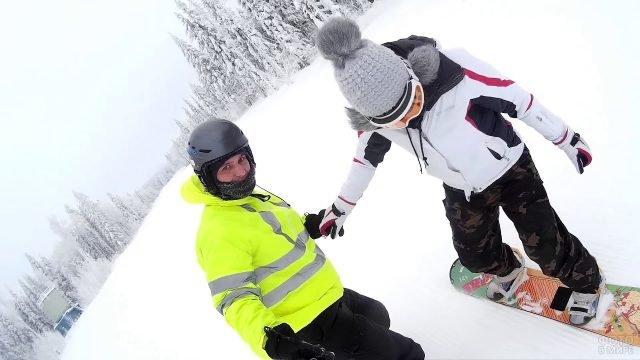 Парень с девушкой учатся кататься на сноуборде