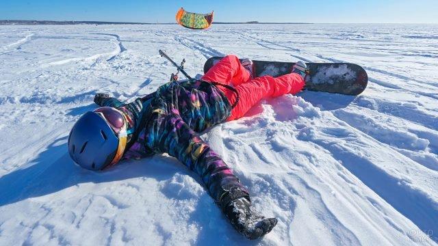 Сноубордист лежит на снегу