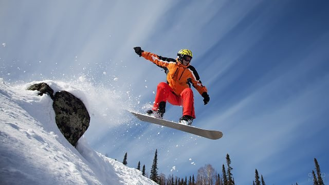 Сноубордист в оранжевом костюме в прыжке