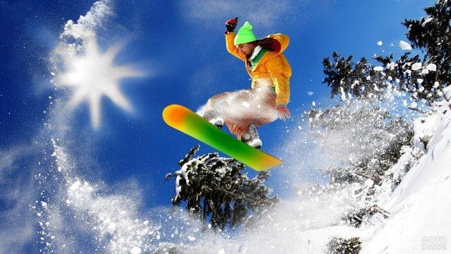 Сноубордист в салатовой шапке в прыжке над елями
