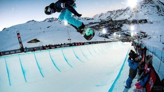 Спортсмен со сноубордом выполняет трюк на соревнованиях