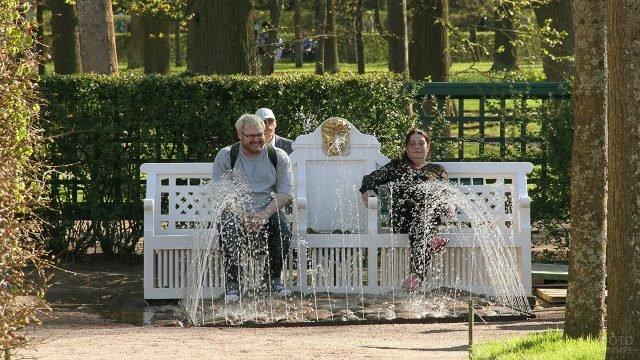 Туристы на фонтане-шутихе Лавочка в Петергофе