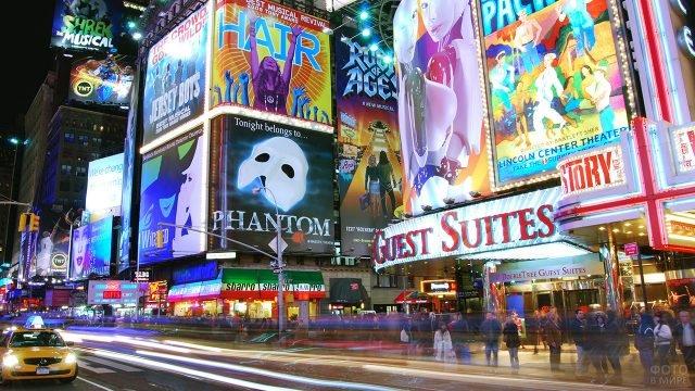 Оживлённое движение на фоне афиш на вечернем Бродвее