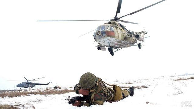 Десантник в снегу под пролетающими вертолётами в ходе учений под Брестом