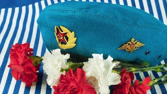 Голубой берет десантника на тельняшке среди гвоздик