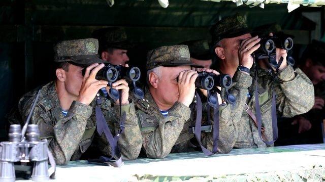 Офицеры ВДВ наблюдают в бинокли ход учений