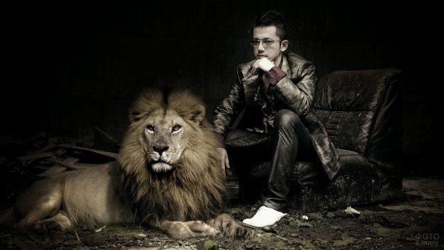 Парень в кресле рядом с лежащим львом