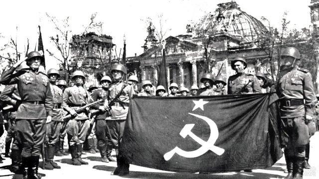 Архивное фото советских солдат с флагом у здания Рейхстага в мае 1945 года