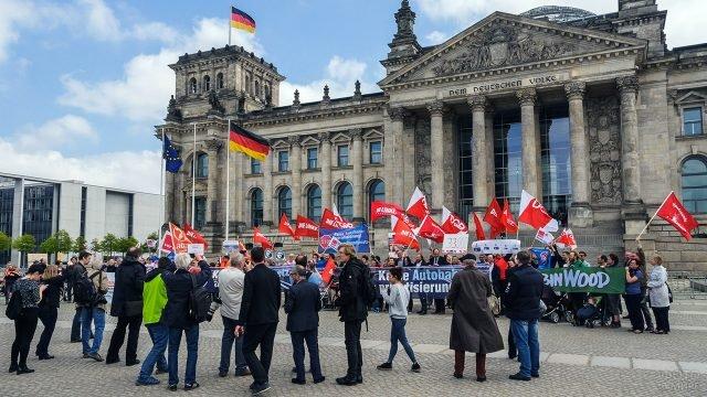 Демонстранты с флагами у здания Рейхстага