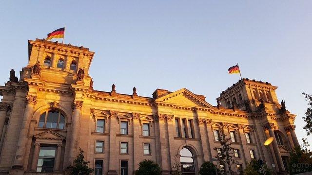 Скульптуры и флаги на здании Рейхстага в лучах вечернего солнца
