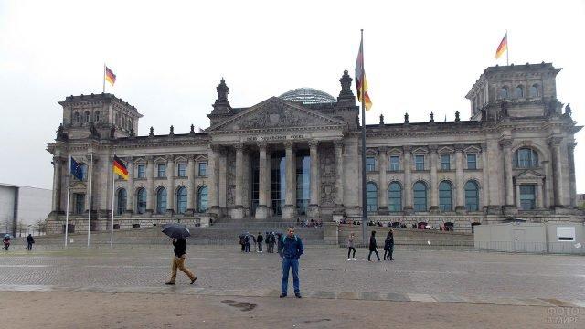 Турист на фоне здания Рейхстага в дождливый день