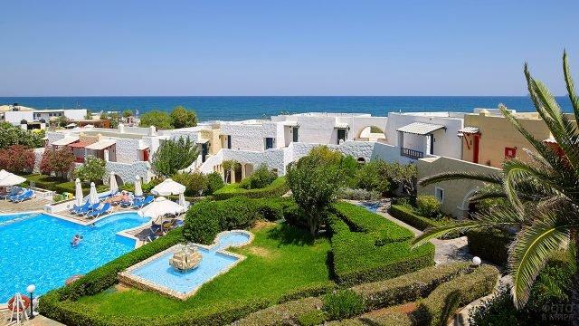 Бассейн и бунгало отеля на побережье острова Крит