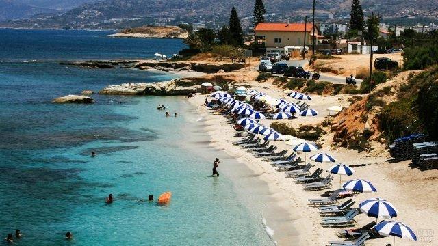 Сине-белые зонтики над шезлонгами уединённого пляжа на острове Крит