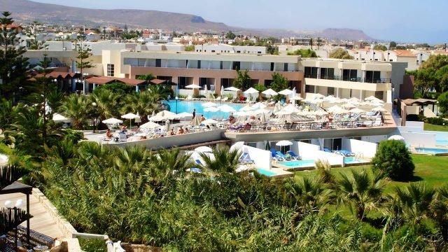 Зелень парка и бассейн при отеле на фоне гор острова Крит