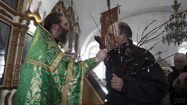 Батюшка и прихожанин с вербой в Вербное воскресенье в православном храме