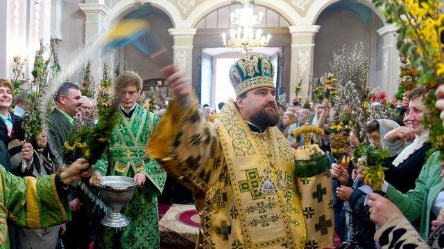 Батюшка проходит по церкви освящая вербу в руках прихожан