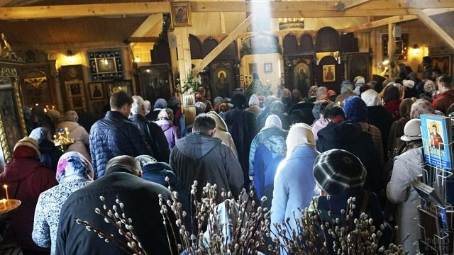 Луч солнца падает на головы прихожан церкви в Вербное воскресенье
