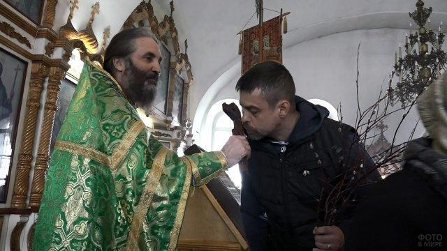 Православный прихожанин церкви целует крест в ходе обряда в Вербное воскресенье