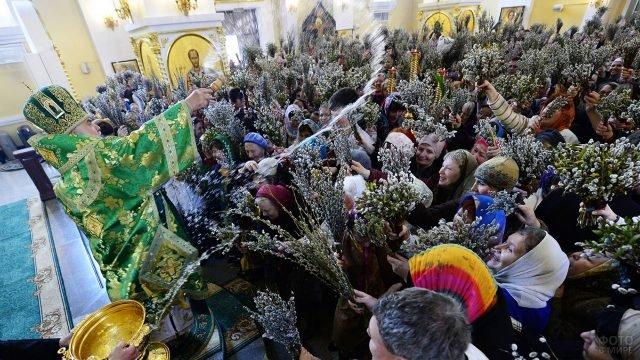 Прихожане с вербой в руках перед батюшкой в православной церкви