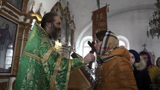 Прихожанка с веткой вербы целует крест во время причастия в Вербное воскресенье